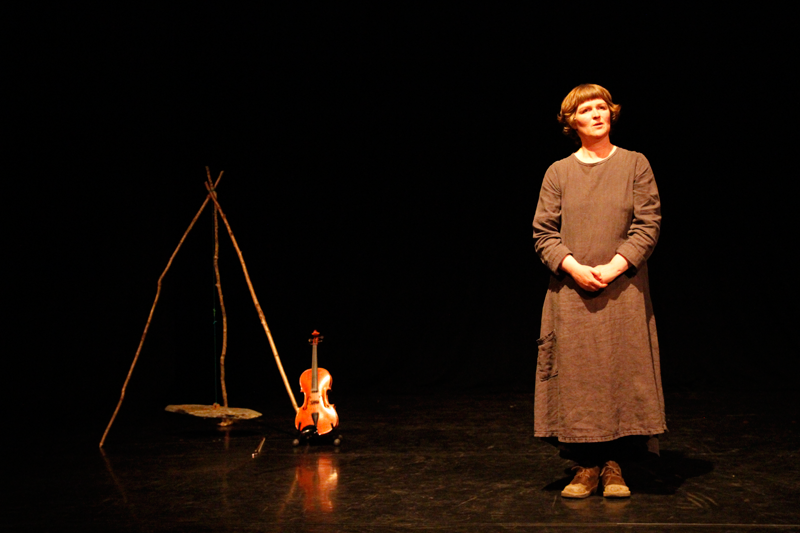 Mairi on a dark stage with her viola and a pendulum