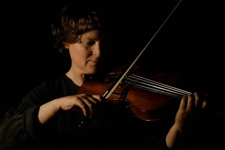 Mairi playing her viola against black background
