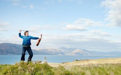 Mairi Campbell on a hillside in warrior pose with her viola